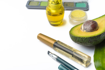 Natural herbal skin care products, top ingredients, avocado, isolated background makeup brushes for face and cosmetic products.