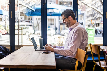 Middle aged businessman in a coffee shop with his computer