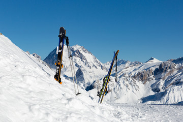Ski equipment with panoramic view of winter mountains on a clear sunny winter day