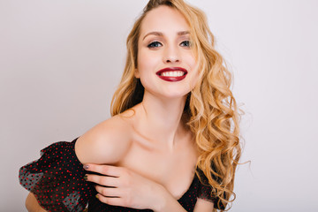 Closeup portrait of young woman, pretty blonde smiling, enjoying, having photoshoot. She has nice soft skin, makeup, long curly hair. Wearing black dress, opened shoulders. Isolated background.