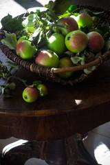 Still mit frischen Bauern-Äpfeln im Weidekorb auf Barocktisch