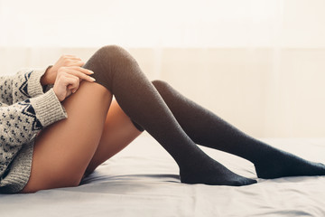 Young girl putting on warm stockings in bed