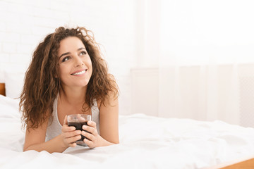 Young woman relaxing on bed with coffee