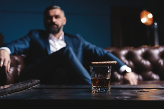 Attractive man with cigar and a glass whiskey