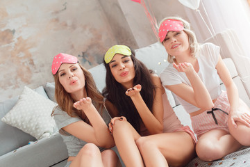 Slumber Party. Young women in sleeping mask together at home sitting on floor sending kiss to camera happy