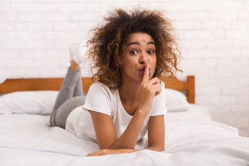 African-american lady showing silence gesture in bed