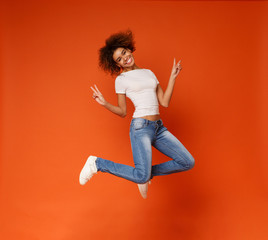 African-american joyful lady jumping and gesturing peace