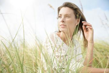 Portrait of attractive woman sitting in wildgrass