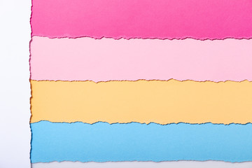 abstract background of multi-colored stripes of torn cardboard , top view,vouchers for writing...