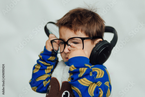 A pretty little boy with headphones and smiling  Fashion home shot