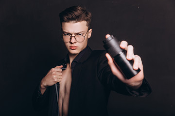 Handsome shirtless man putting deodorant. image of young man using deodorant isolated - Image. Handsome young man with deodorant on dark background - Image