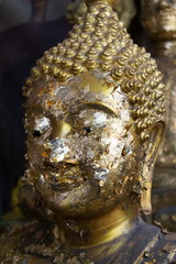 Face Buddha statue with gold plate attached to many.