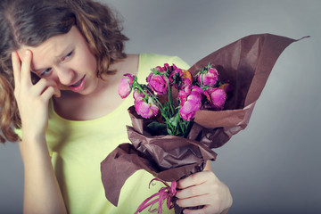 Girl holds a bouquet of wilted flowers