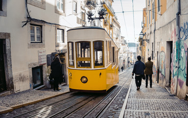 LISBON, PORTUGAL - January 16, 2019: Tourist photographing a famous retro yellow tram on the street in Lisbon city, Portugal