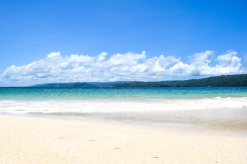 island with white beach blue turquoise ocean and waves, blue sky with some clouds, paradise island at cayo levantado