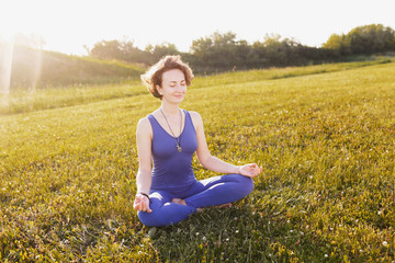 Charming young slim woman doing yoga and meditates with closed eyes and I am on the green grass in the park sunny summer day. Concept of spiritual cleansing and relaxation. Advertising space