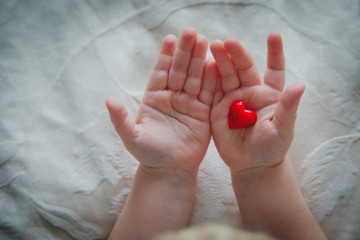 love and family. little baby holding heart in hands