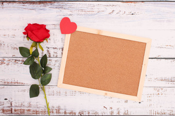 Roses and red hearts and blank frames on wooden floors