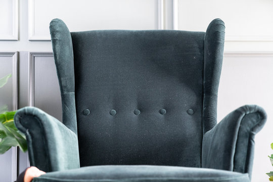 Close up high back green velvet armchair with gray painted wall in the background / interior concept / empty space for advertising