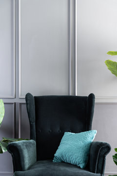 Close up high back green velvet armchair and blue pillow with gray painted wall in the background / interior concept / empty space for advertising
