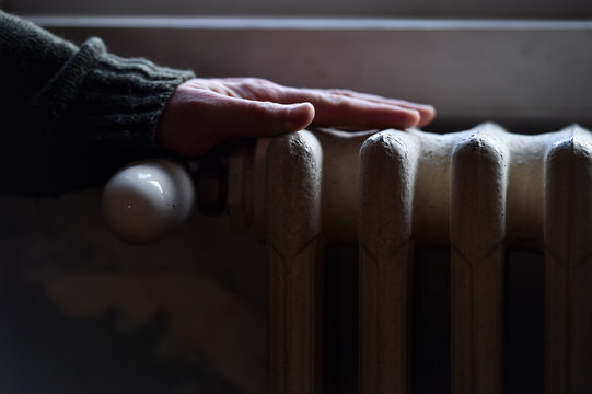 Hand checking the heat coming from a household radiator