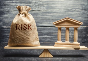 A money bag with the word Risk and a bank building on the scales. The concept of financial and economic risk. Unreliable investment. Unpaid loan. Financial risk management. Commercial loan Wall mural