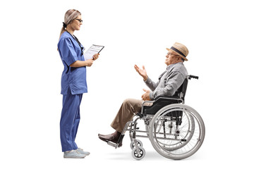 Young female nurse talking to an elderly gentleman in a wheelchair