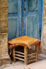 Kleiner Hocker vor blauer Tür in der Medina von Essaouira, Marokko.
