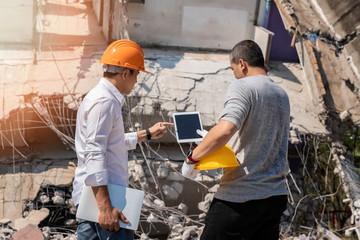 Demolition control supervisor and foreman discussing on demolish building.