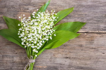 Beautiful bouquet of lilies of the valley flowers on the old wooden background with copy space