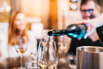 Waiter pouring wine in glass for guests at table in bar restaurant party