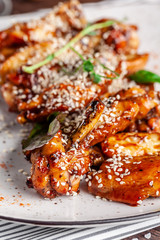 American cuisine concept. Fried glazed chicken legs with sesame on a white plate with chilli peppers. Background image for a menu in restaurants or cafes. copy space