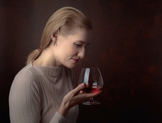Portrait of a beautiful woman with glass of brandy.