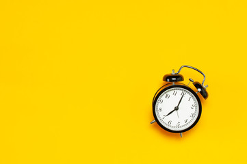 Black retro alarm clock on yellow background top view Flat lay copy space. Minimalistic background, concept of time, deadline, time to work, morning
