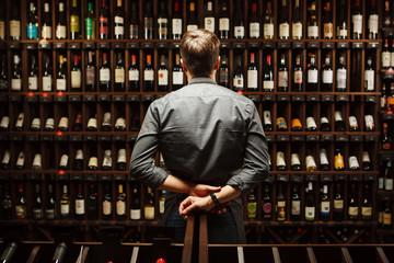 Fototapeta Bartender at wine cellar full of bottles with exquisite drinks