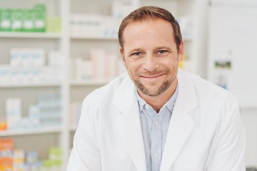 Smiling friendly pharmacist in a drugstore