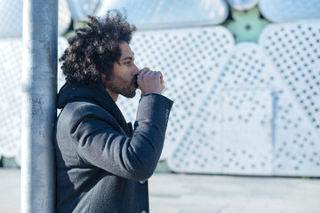 Portrait of cheerful handsome afro man in casual wear posing for the camera bearded young man holding take away coffee in hand outdoors