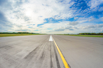 Runway clear for take off, airstrip with marking on blue sky with clouds background. Travel aviation concept