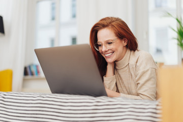 Young woman working on her laptop with a smile