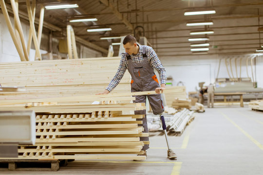 Disabled young man with an artificial leg is working at furniture factory