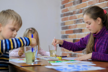 Happy children - boy and two girls is drawing with colorful paint