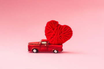 Valentine's Day concept. A small red car figurine carries a heart on a pink background. Congratulations card. Selective focus
