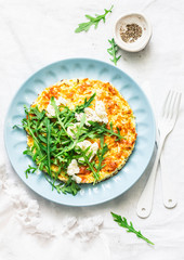 Summer squash frittata with goat cheese and arugula - delicious healthy diet food on a light background, top view