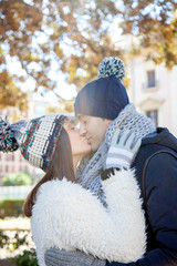 Young couple dressed in winter clothes and wool hats kiss passionately in a public park
