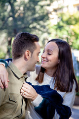 A young couple in love flirts in a public park