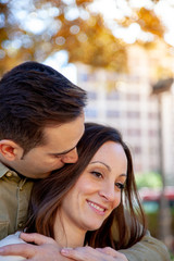 A man hugs and kisses his young wife from behind in a public park