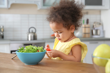 Cute African-American girl eating vegetable salad at table in kitchen