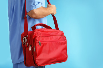 Male doctor with first aid kit and space for text on color background, closeup. Medical object