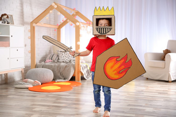 Cute little boy playing with cardboard armor in bedroom