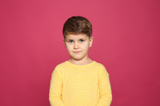 Portrait of cute little boy on color background